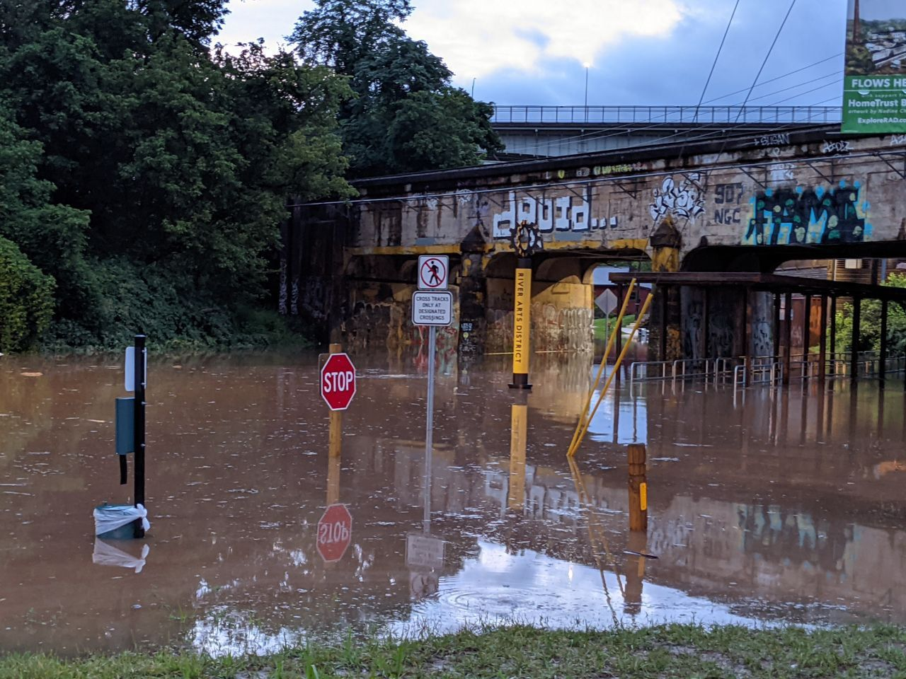 """Flooded street with railroad bridge over top. Stop sign and public trashcan peek over top of the water. Bridge has a sign that reads """"River Arts District"""""""