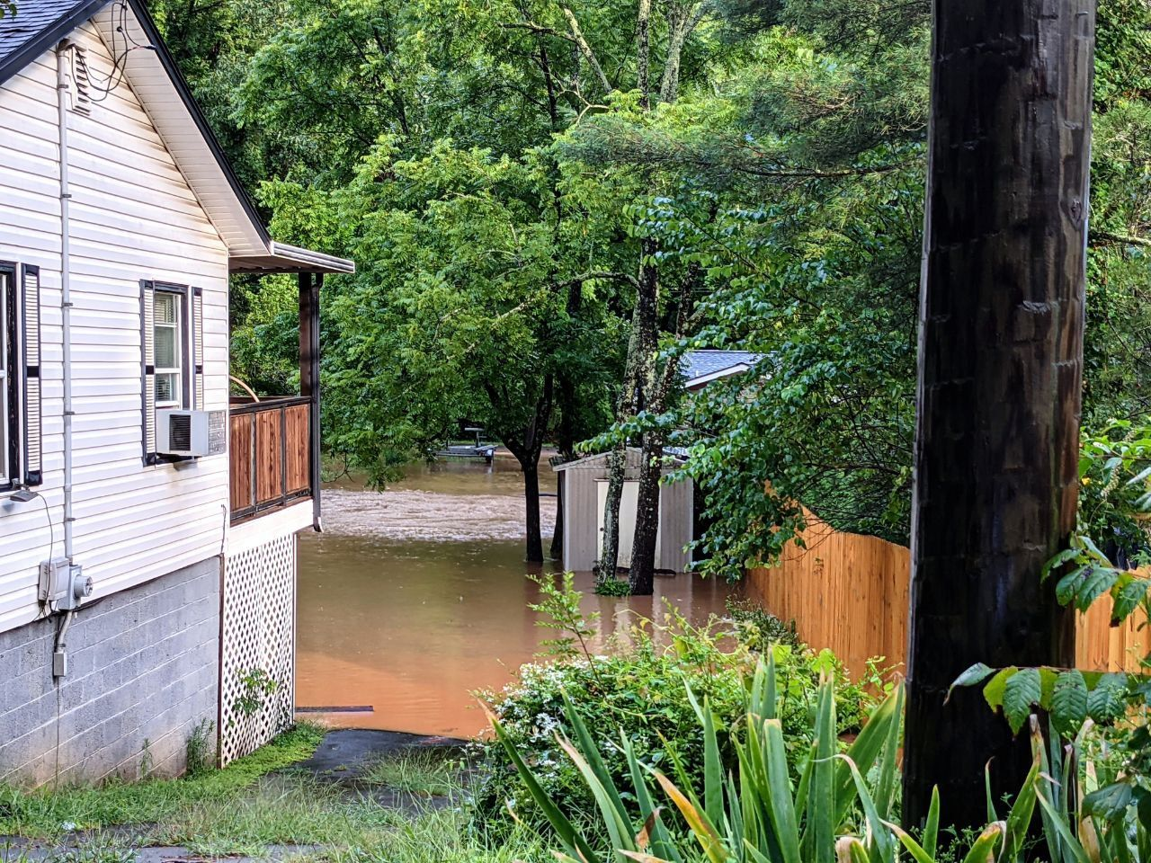 White house on left side of frame, the house's backyard is flooded.Sheds and other houses are submerged in the water.